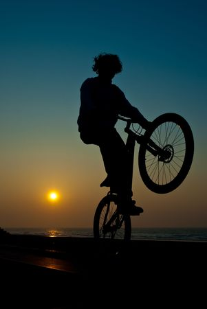 young man performing bike tricks at sunset photo