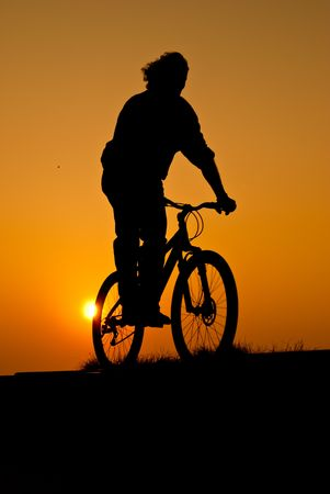 silhouet of a young adult riding a bike at sunset photo