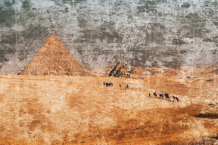 Faded picture of camel caravan in the Sahara desert moving to the pyramid