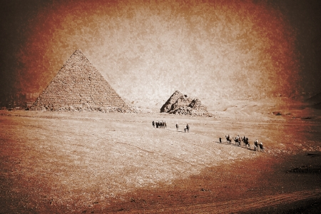 Faded picture of camel caravan in the Sahara desert moving to the pyramid photo