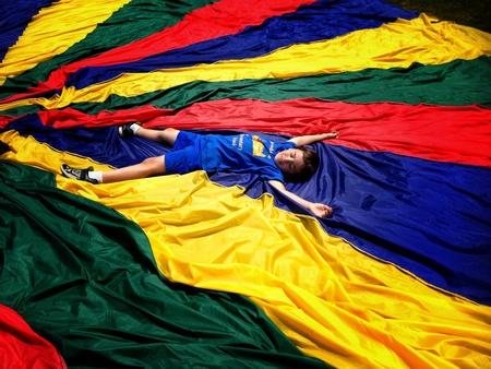 A boy lying down on colourful cloth