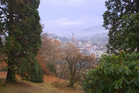 German small town. Rainy autumn is in city park.The city is seen through a fog