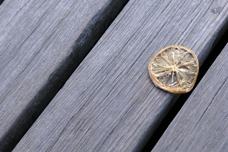 The withered segment of a lemon lies on a wooden flooring Stock Photo