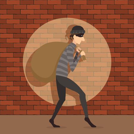 The thief or burglar carries a large sack. Robber in dark clothes with full bag on brick wall background. Dangerous masked criminal.