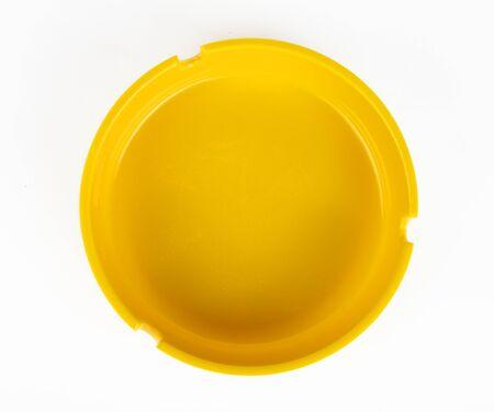 Yellow round ashtray on a white background isolate