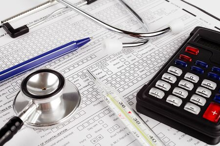 Healthcare costing. Medical phonendoscope, calculator, pen, medical thermometer.
