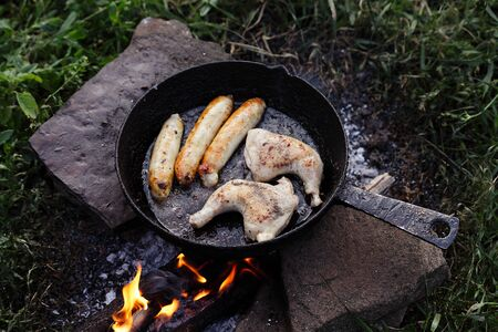 sausages chicken legs fry on a fire in a pan, cooking in nature Stock Photo