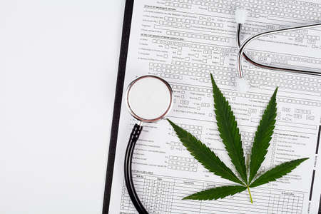 Marijuana leaf, medical stenandoscope on a white background, place for text Stock fotó