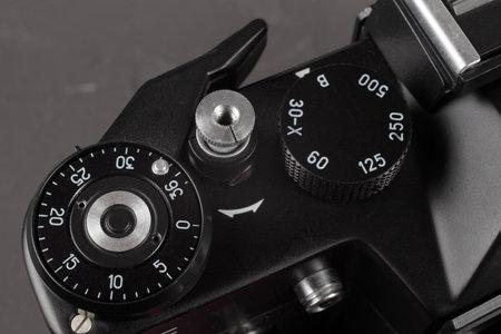 Old film SLR camera, shutter cocking wheel, frame counter and shutter button, close-up, selective focus Foto de archivo