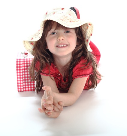 the little girl lies in a hat and smiles photo