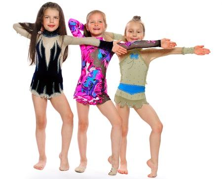 drie turners van het meisje van 6 jaar uit te voeren oefeningen geïsoleerd op wit