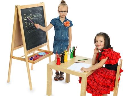 dos ni�as juegan en el aislamiento escolar sobre un fondo blanco Foto de archivo - 15328240