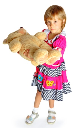 the girl embraces a big toy bear in studio on a white background photo