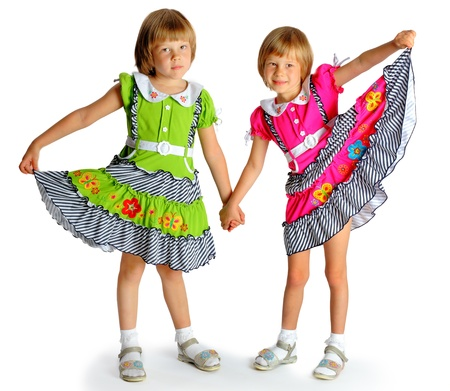 6 years girl: sisters twins in yellow bright dresses have fun in studio