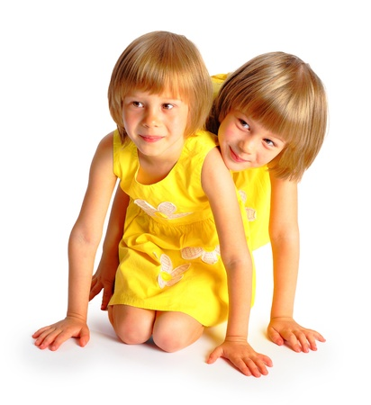 10 years girls: sisters twins in yellow bright dresses have fun in studio