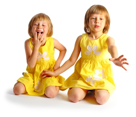age 5: sisters twins in yellow bright dresses have fun in studio