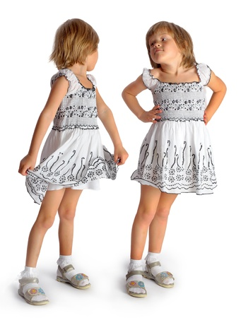 sisters twins in white dresses play in studio on a white background