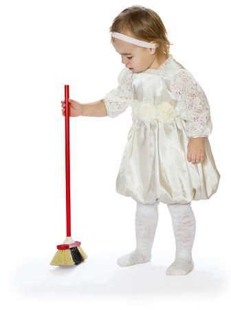 sweeps: the little girl sweeps a floor the isolated