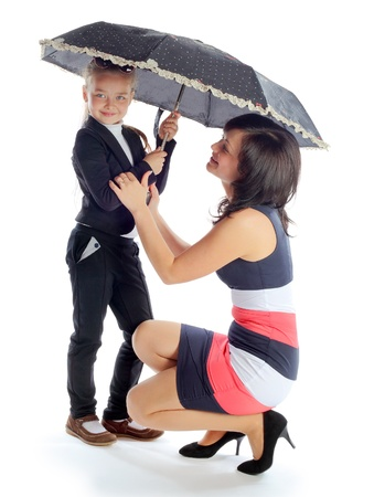 mother and the daughter under a big umbrella isolated white background Stock Photo - 16972001