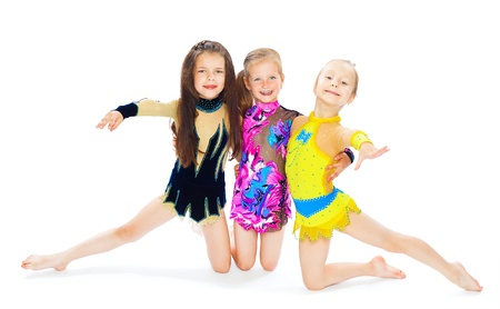 carry out: three gymnasts of the girl of 6 years carry out exercises isolated on white