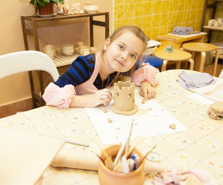 Little girl sculpts a toy from clay with enthusiasm photo