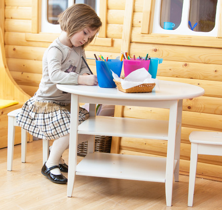 early childhood: A young girl is sitting at a round table and draws a pencil on paper. Stock Photo