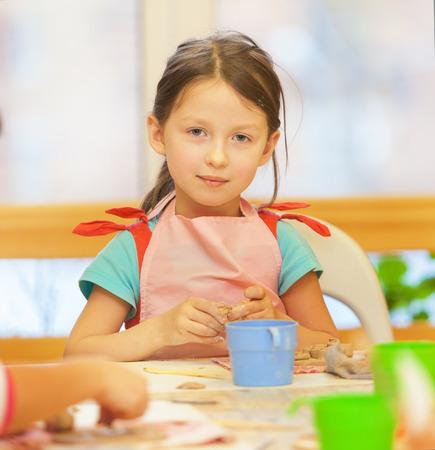 nurser: little girl sculpts figures out of clay. (ceramic)