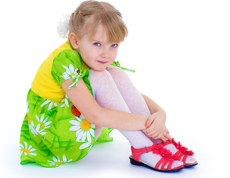 hugging knees: little girl sitting hugging her knees and smiling cheerfully. Isolate on white background