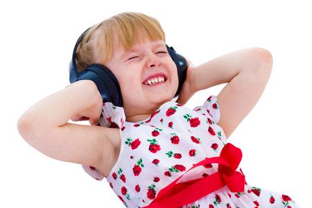 babyface: Charming little girl loves to listen to music through headphones.Isolated on white background.