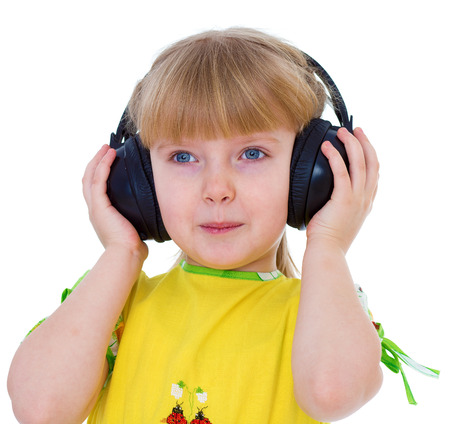 Charming little girl loves to listen to music through headphones.Isolated on white background.