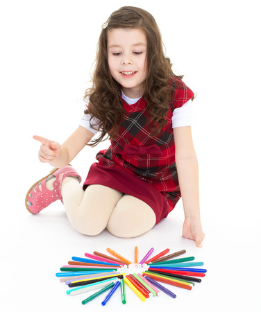 girl tongue: little girl sitting on the floor and playing with colored pens.Isolated on white  .