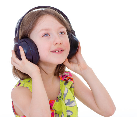 Portrait of cute 7 years girl wearing headphones over a white background photo