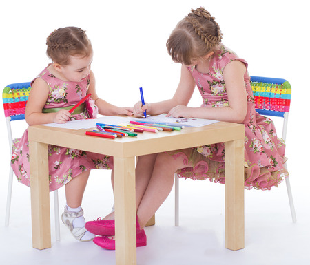 Two little girls in kindergarten paint markers while sitting at table.isolated on white background photo