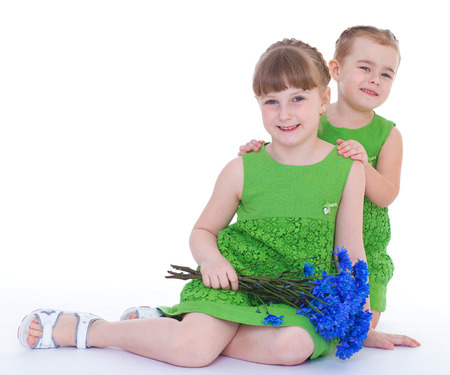 coy: two beautiful little girl with a beautiful bouquet of blue flowers. Stock Photo
