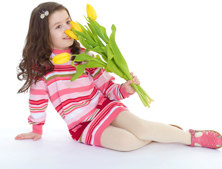 Kids,girl,kid,child- Charming schoolgirl sitting on the floor with a bouquet of yellow flowers. Isolated on white background. photo