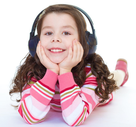 Kids,girl,kid,child- charming and very musical little girl is listening to music. Isolated on white background. photo