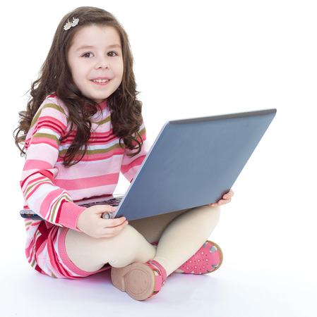 Kids,girl,kid,child- Portrait of adorable little girl sitting on the floor with a laptop. Isolated on white background. photo
