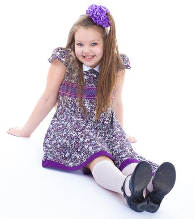 zapatos escolares: chica, medias, la sonrisa y la alegría -. encantadora niña que se sienta en el suelo. aislado en el fondo blanco.
