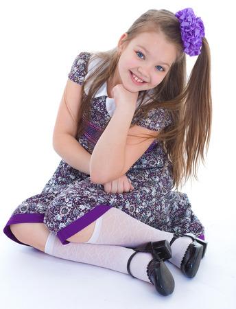 uniform skirt: girl, stockings, smile and joy.- charming little girl sitting on the floor. isolated on white background.