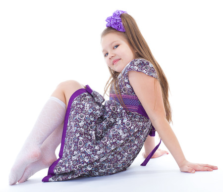 blusa: chica, medias, la sonrisa y la alegría -. encantadora niña que se sienta en el suelo. aislado en el fondo blanco.