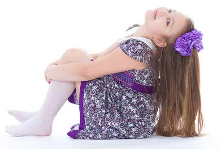 girl, stockings, smile and joy.- charming little girl sitting on the floor. isolated on white background. photo