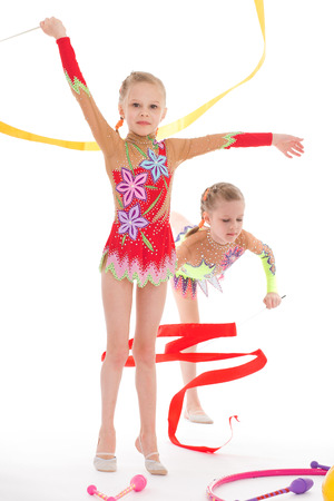 twins, kids, girls, gymnast, sport- adorable twin girls gymnasts. Isolated on white . photo