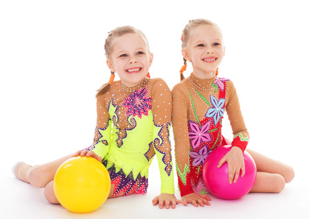 future twin: twins, kids, girls, gymnast, sport- adorable twin girls gymnasts. Isolated on white . Stock Photo