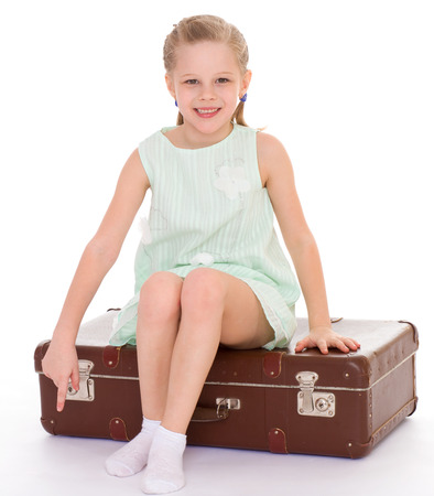 Summer, suitcase, travel, vacation, baby girl -happy little girl with a big and very old suitcase. Isolated on white . photo