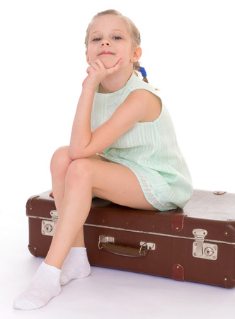 Summer, suitcase, travel, vacation, baby girl -happy little girl with a big and very old suitcase. Isolated on white background. photo
