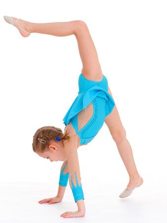 jong meisje doet gymnastiek op een witte Stockfoto