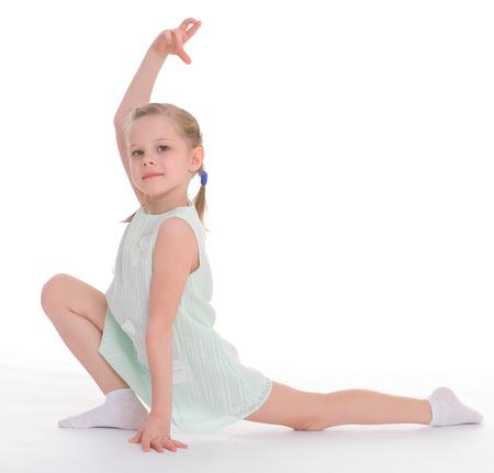 young girl doing gymnastics over white  photo