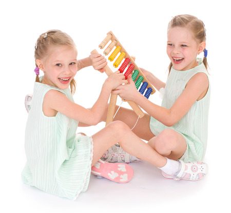 playgroup: Cute sisters work in the Montessori environment  Isolated on white background  Stock Photo