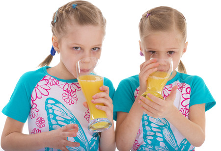 twin sisters love to drink orange juice. Isolated on white background. photo
