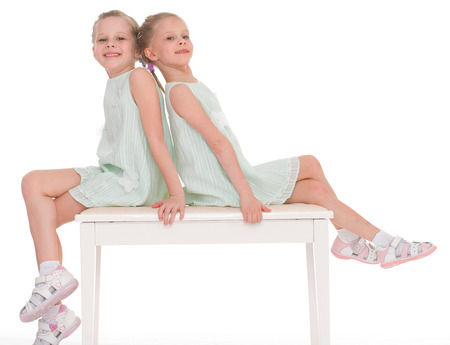 Cute sisters having fun sitting on a chair.Isolated on white background. photo